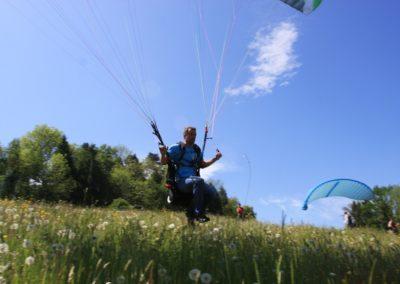 Gleitschirmflieger an einem sonnigen Tag auf einer Blumenwiese