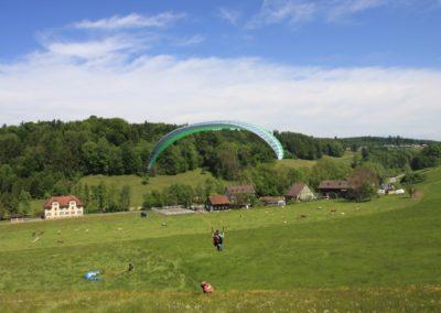 Erste Flugversuche in kleinen Höhen. ein Paraglider gleitet wenige Meter über dem Boden den Hang hinab.