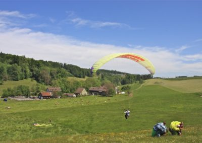 Zwei Gleitschirmflieger laufen den Berg hinauf. Ein dritter erlebt Gleitschirmfliegen Hautnah